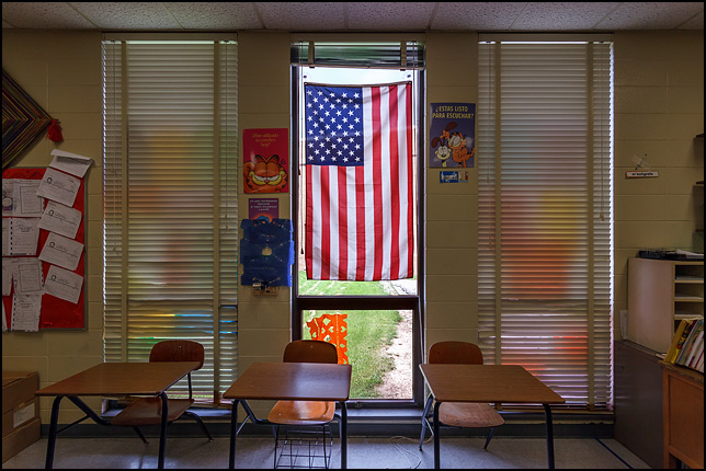 An American flag hangs in the window of a middle-school foreign-language classroom, flanked by Spanish posters of Garfield the Cat. Three student desks sit in front of the windows.