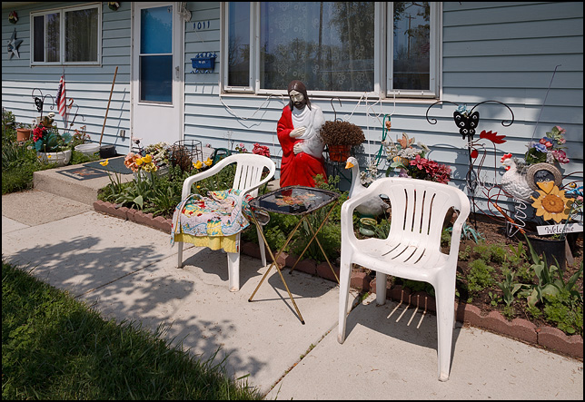 A large plastic statue of Jesus Christ stands amid a large number of lawn decorations with two plastic patio chairs in front of a ranch-style house on Wakefield Drive in the Northcrest neighborhood in Fort Wayne, Indiana.