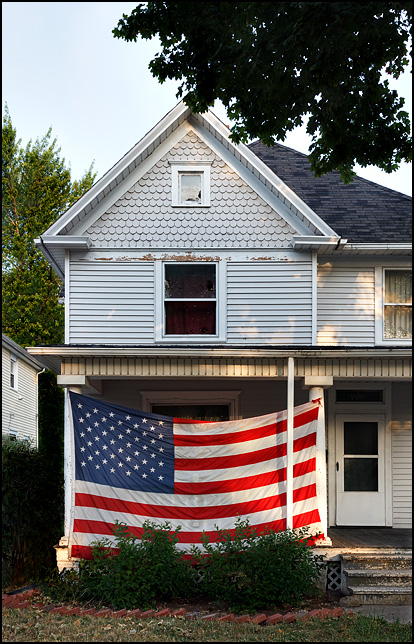 An old Victorian house with a huge American flag covering most of the front porch at the corner of Broadway and Home Avenue in Fort Wayne, Indiana.