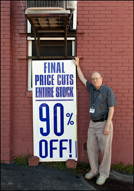 Bill Christie, owner of Sunny Schick Camera Shop in Fort Wayne, Indiana. He is standing next to the 90 percent off sale sign on the day the store closed its doors.