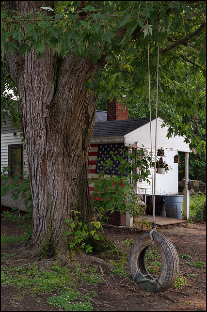 An old tire swing hanging from a tree in front of a small house on Huron Street in a working class neighborhood in Fort Wayne, Indiana. A large American flag covers the side of the front porch.