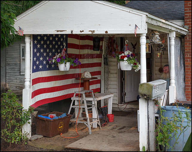 A huge American flag screens one side of the porch on a small white house with several hanging flower pots in Fort Wayne, Indiana. An old man with a big beard sits at the back of the porch and a plastic skull sits an a pedestal on a table in front of the flag.