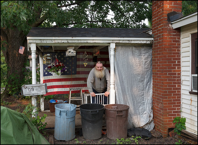 An old man with a big beard stands in front of a large American flag on the front porch of his house on the working-class west side of Fort Wayne, Indiana.