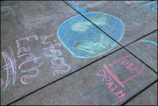 Drawings and religious messages written in sidewalk chalk on the pavement of Freimann Square in Fort Wayne by Mormon missionaries. This one has an arrow pointing from BIRTH to LIFE ON EARTH to DEATH. There is a drawing of the earth and a tombstone.