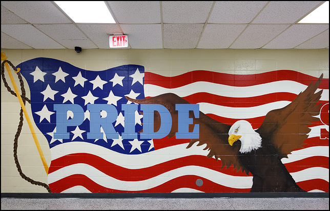 A patriotic mural in a middle school hallway depicting a bald eagle and American flag with the word Pride superimposed over the flag.