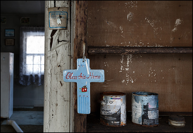 A ceramic cross hanging from shelves built in to the wall of an abandoned house. The cross says Bless This Home. Cans of paint sit on the shelf.