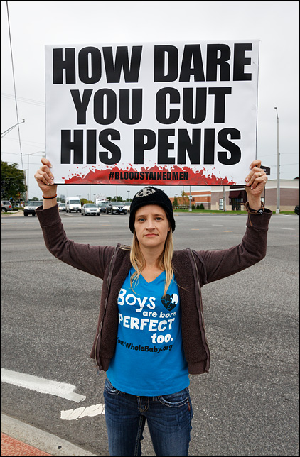 A woman holding a sign at a protest against infant circumcision at the corner of Coldwater Road and Coliseum Boulevard in Fort Wayne, Indiana. Her sign says, How Dare You Cut His Penis.