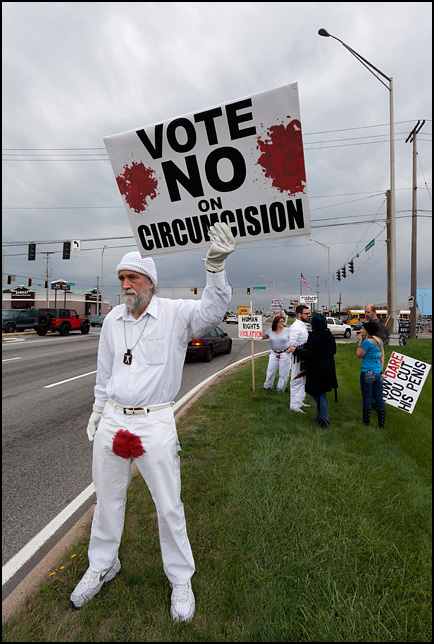 An old man with a long beard holding a sign that says Vote No On Circumcision at a protest against infant circumcision in Fort Wayne, Indiana. His white pants have a red bloodstain on the crotch. Bloodstained Men.