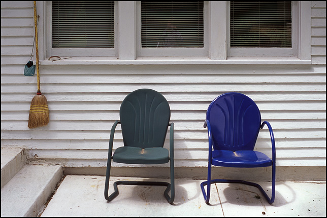A pair of metal motel chairs, one blue and one green, sit under a window behind a white farmhouse in rural Indiana. A broom and a fly swatter hang from the window frame next to the chairs.