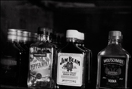 Liquor bottles in the display case next to the counter at Mary's Bar in Cerrillos, New Mexico. The three bottles are Hiram Walker Peppermint, Jim Beam Kentucky Bourbon whiskey, and Wolfschmidt vodka.