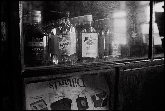 Liquor bottles in the display case next to the counter at Mary's Bar in Cerrillos, New Mexico. The three bottles are Hiram Walker Peppermint, Jim Beam Kentucky Bourbon whiskey, and Wolfschmidt vodka. An old Dillard's department store ad covers the glass on part of the counter.