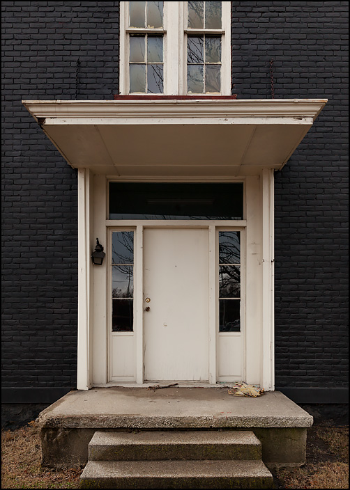 The front door of a vacant house on Broadway in Fort Wayne, Indiana. The brick house is painted black, with white door and windows.