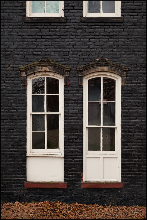 The windows on the side of a vacant house on Broadway in Fort Wayne, Indiana. The brick house is painted black, with white window frames topped by ornately carved lintels.