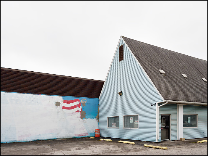 A partially painted-over mural of the Statue of Liberty and an American Flag adorn a wall next to a vacant building on Broadway in Fort Wayne, Indiana.