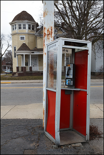 An old neglected telephone booth stands on the sidewalk next to a signpost on Broadway in Fort Wayne, Indiana.