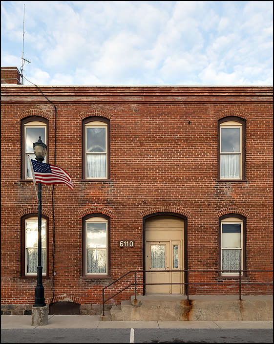An American flag flies from a light pole in front of the entrance to an apartment in a brick building on Bronson Street in the small town of Orland, Indiana. The apartment has lace curtains in the windows.
