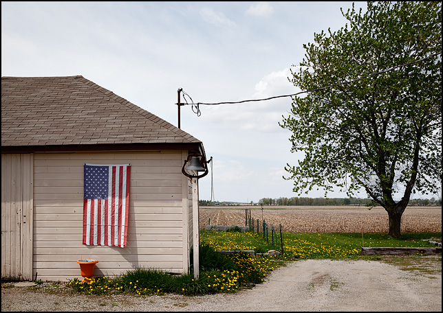An American flag hangs vertically on the garage behind a farmhouse on State Road 1 in rural Wells County, Indiana. An old school bell is mounted on a pole next to the garage.