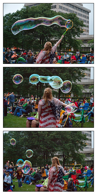 A young woman wearing an American flag shirt blowing giant bubbles on the Fourth of July in the crowd on the Courthouse Green in Fort Wayne, Indiana.