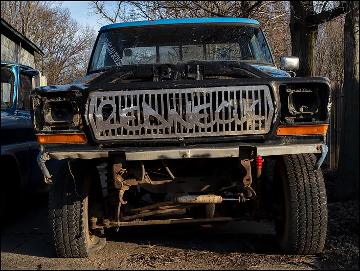 A blue late 1970s Ford F-150 pickup truck with a grille that says Redneck in the small town of Burr Oak, Michigan.