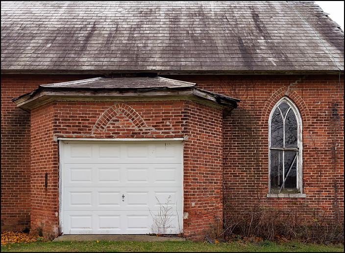 A garage door in the apse of an abandoned brick Methodist Church in Butler Center, Indiana.