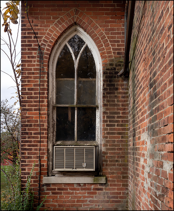 A pointed arch window on the front of an abandoned brick Methodist Church in Butler Center, Indiana. There is an old Fedders air conditioner in the window and ivy growing on the bricks.