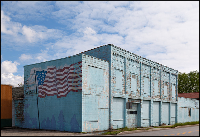 A mural of an American flag flying above American soldiers, painted on the side of an old cinderblock industrial building on Main Street in the small town of Butler, Indiana. This is the former Engineered Materials Incorporated building.