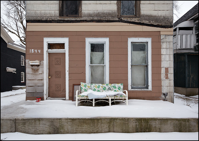 A patio sofa sits covered in snow on the front porch of a vacant house on Broadway in Fort Wayne, Indiana.