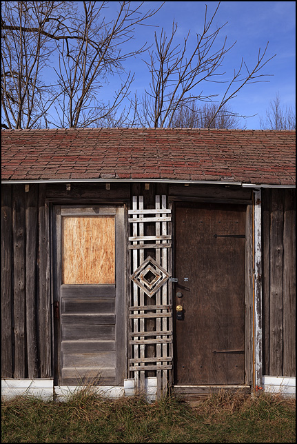 A wooden trellis stands between the locked and boarded-up doors of a small cabin on US-33 just south of Benton in rural Elkhart County, Indiana.