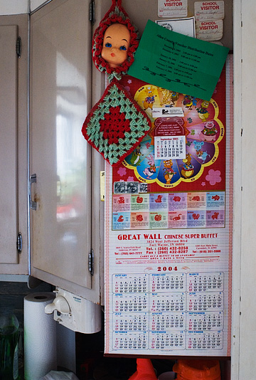 A kitchen cabinet in my grandfather's old house. The cabinet door is covered with a calendar from the Great Wall Chinese Buffet, a doll's head, and several name tags from when he visited his grandchildren at school.
