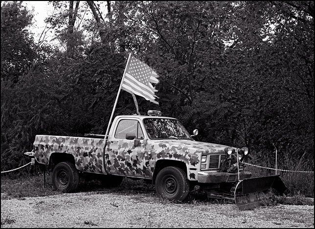 A torn-up faded old American flag on an old GMC pickup truck with hand-painted leaf-pattern camouflage and a snow plow.