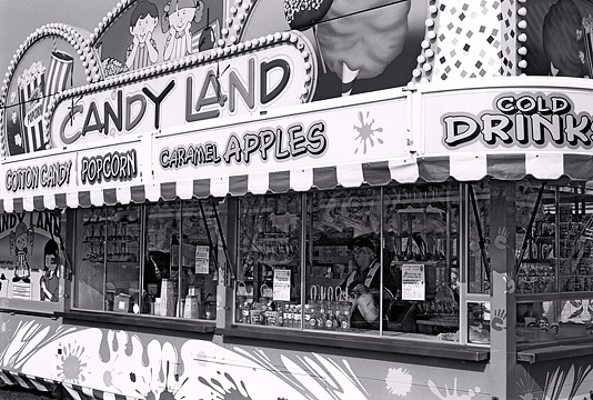 Candyland concession stand selling caramel apples, popcorn, soft drinks, and cotton candy at the Three Rivers Festival midway in Fort Wayne.