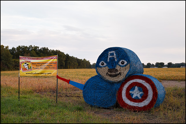 A stack of round hay bales painted to look like the comic book character Captain America.