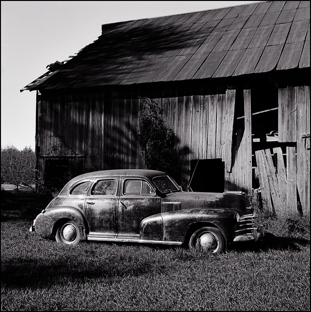 A black 1947 Chevrolet sedan in front of an old barn on a farm in Allen County, Indiana. The windmill casts a shadow on the barn behind the car.