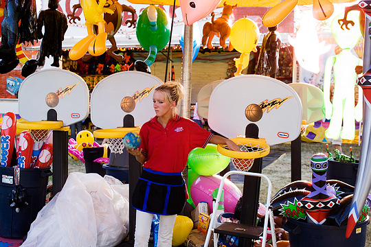 A carnival worker standing in front of Little Tykes basketball toys surrounded by plush stuffed animals used as carnival prizes at the basketball game at the Three Rivers Festival carnival in Fort Wayne.
