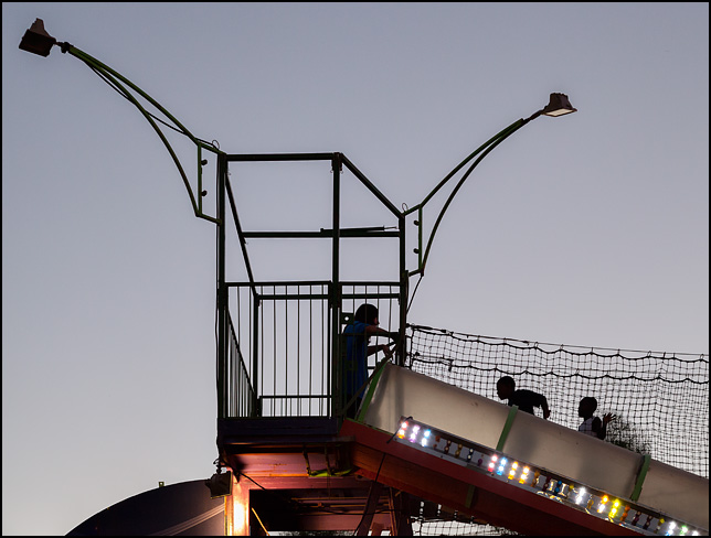 Two kids silhouetted against the evening sky walk across a suspension bridge to the top of an enclosed slide at the Three Rivers Festival carnival in Fort Wayne, Indiana.
