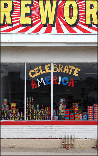 The front window of a fireworks store on Main Street US-33 in the small town of Churubusco, Indiana. A sign made of cut-out paper letters says, Celebrate America.
