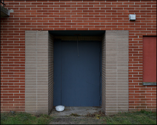 A Boarded-up entrance to one of the vacant buildings at Centlivre Village Apartments in Fort Wayne, Indiana. A white pet food bowl sits on the ground in front of the door.