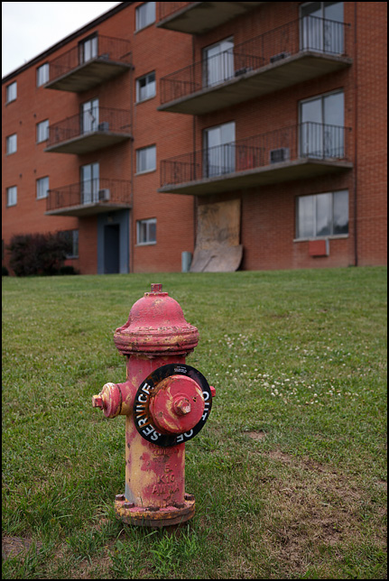 An old fire hydrant with peeling paint and an Out-Of-Service sign on it stands in front of one of the vacant buildings at Centlivre Village Apartments in Fort Wayne, Indiana.