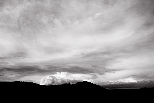 Sunset over the Cerrillios Hills on the Turquoise Trail in New Mexico. The mountains are silhouetted against the dramatic sky.