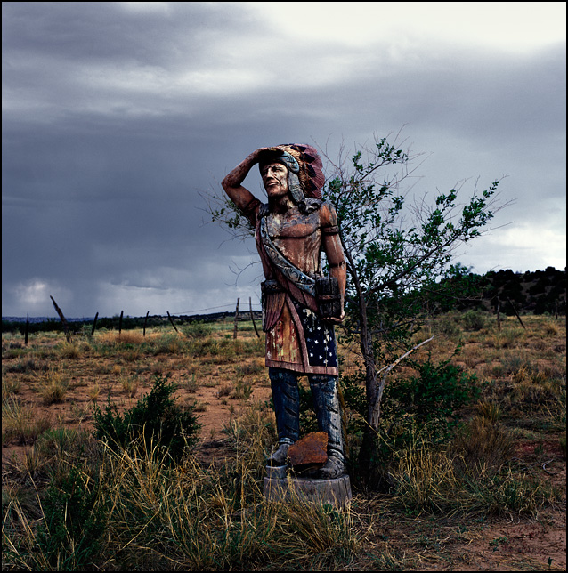 A wooden cigar store Indian standing in the New Mexico Desert near Cerrillos under a dark stormy sky.