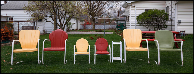 Two child-size metal motel chairs sit in a line flanked by four adult-size motel chairs behind a house in Fort Wayne, Indiana.