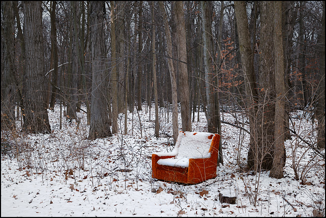 Snow covers an old orange upholstered chair that sits alone in a forest in Indiana.