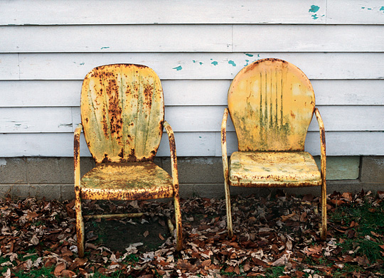 My grandparents rusty old yellow metal motel chairs sitting next to his house in the rain.