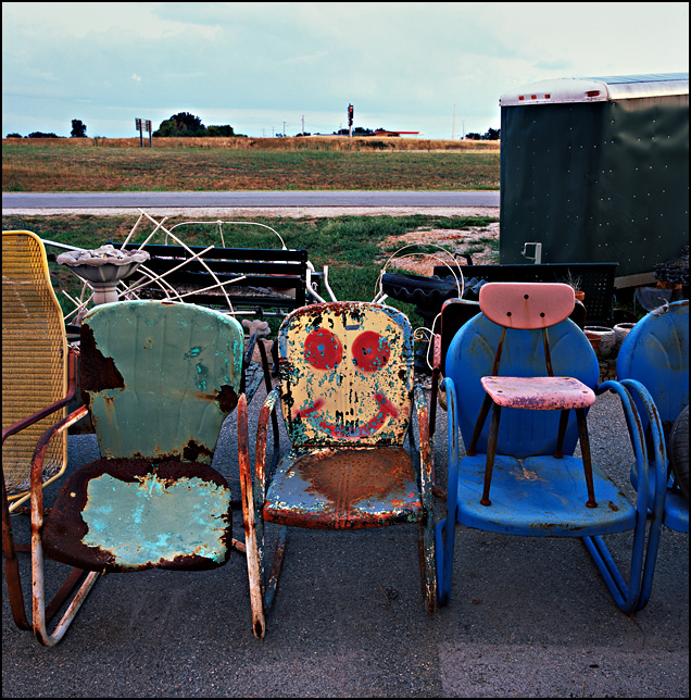 A happy face spray-painted on one of the old metal chairs among the junk in front of the the Cimmaron Antique Mall on I-44 in Missouri.