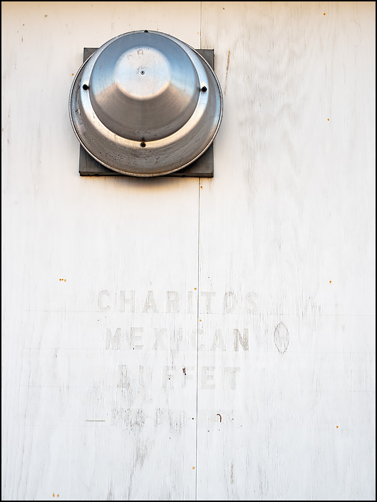 A metal vent hood sticks out from the front of the former Charitos Mexican Buffet, whose painted-over name is still visible on the front of the building on Wayne Street in the small town of Waterloo, Indiana.