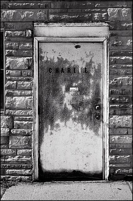 A rusty old steel door with the name Charlie's spelled out in vinyl letters on it. The door is on an abandoned restaurant on East Washington Boulevard in the inner city area of Fort Wayne, Indiana.