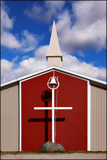 A large white cross with a bell on top of it stands in front of Charter Oak Church at the corner of County Road 500S and County Road 300E in Green Center, Indiana. The church is a plain modern steel building, painted red and tan.