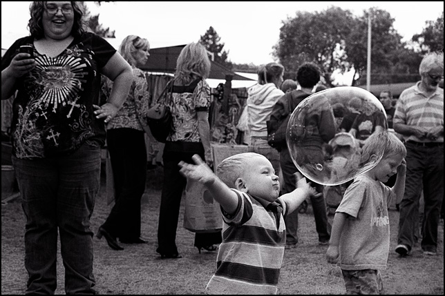 A little boy running toward a huge soap bubble with his arms opened wide to grab it.