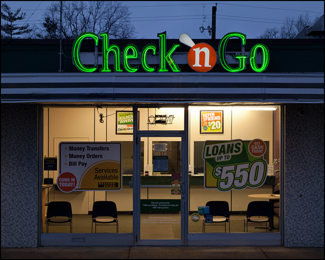 Neon signs glow in the early morning at a Check-N-Go payday loan store on South Calhoun Street in Fort Wayne, Indiana.