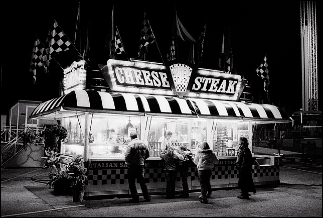 Customers gather around the windows waiting for their food while checkered racing flags fly from the top of the brightly lit Cheese Steak Diner during a late night carnival.